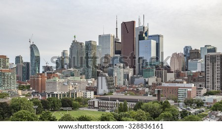 TORONTO, CANADA - JUNE 26, 2015: Evening  view from a high-rise building of Moss Park Arena with nearby buildings,Toronto's Financial District skyscrapers and CN Tower apex at the background. - stock photo