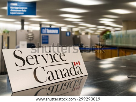 TORONTO,CANADA-JUNE 25,2015: Service Canada Signage placed on a desk with blurred indoor office space in the background. Service Canada is the main service provider to residents in the country - stock photo