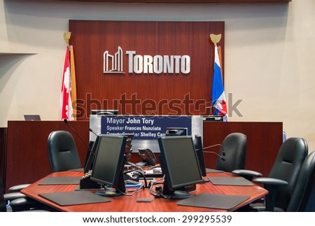 TORONTO,CANADA-JUNE 25,2015: Toronto Council Chamber inside the new city hall, seat of the mayor flanked by the national and provincial flag, with a view of the seat of the city clerk  - stock photo