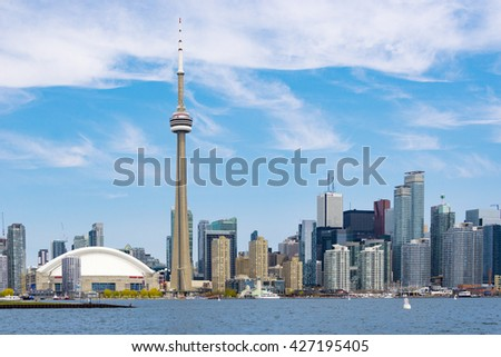 TORONTO,CANADA-MAY 21,2016: CN tower in Toronto skyline seen from Lake Ontario. The city offers boat tours which are very popular with tourists and visitors to the Financial Capital of Canada - stock photo