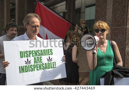 TORONTO,CANADA-MAY  27,2016:Marc Scott Emery (holding sign) and Tracey Curley (green dress) leading the protest against Project Claudia.  Project Claudia was a crack down on pot dispensaries - stock photo