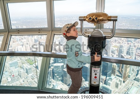 TORONTO, CANADA - MAY 7, 2007: Small unidentified boy trying to use the telescope on the observation deck of the CN tower. CN Tower is 553 m high concrete communications and observation tower in downtown Toronto. - stock photo