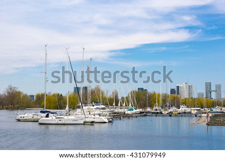 TORONTO,CANADA-MAY 24,2016: White boats anchored at the harbour. The city offers boat tours which are very popular with tourists and visitors to the Financial Capital of Canada