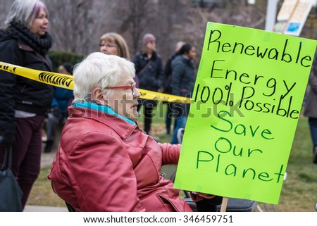 TORONTO,CANADA-NOVEMBER 29,2015:Elder senior woman with sign during Global Climate March in Toronto. Hundreds march  demanding the government to actually act on emissions and other climate issues - stock photo