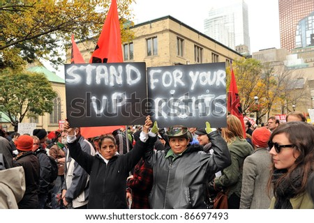 TORONTO, CANADA – OCT 15:  Unidentified demonstrators march to Saint James Park for the Toronto version of Occupy Wall Street, Oct. 15 2011.  The bank buildings on Bay Street are in background. - stock photo