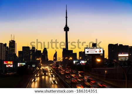 TORONTO,CANADA-OCTOBER 9, 2013: CN Tower at dawn as seen from the QEW. One of the highest structures in the world and a tourist landmark - stock photo