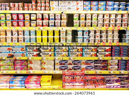 TORONTO, CANADA - OCTOBER 31, 2014: Different brands of yogurt on shelves in a supermarket. Yogurt is nutritionally rich in protein, calcium, riboflavin, vitamin B6 and vitamin B12. - stock photo