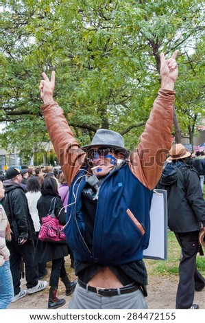 TORONTO,CANADA-OCTOBER 18,2011: Occupy Toronto Movement: Man with a cigarette in his mouth raised his hands up with the sign of victory. In the background is a protest of people - stock photo