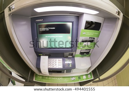 TORONTO,CANADA-OCTOBER 2, 2016: TD bank: Automated Teller Machine (ATM) printing out a slip. The TD bank is the second largest in Canada
