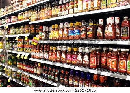 TORONTO, CANADA - SEPTEMBER 13, 2014: Sauces and tomato ketchup bottles on shelves in a supermarket. Europe and North America are the leading consumers of sauces, dressings and condiments in the world - stock photo