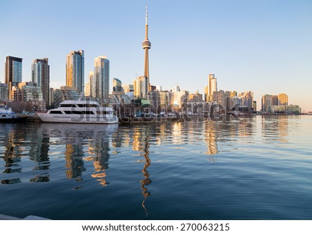 TORONTO, CANADA - 16TH APRIL 2015: Part of the Toronto waterfront at sunset, showing buildings, offices, the CN Tower and boats. Reflections are in the water. - stock photo