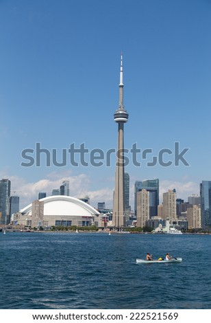 TORONTO, CANADA - 27TH JULY 2014: The CN Tower and Rogers Centre from Lake Ontario during the day with people in a canoe in the foreground - stock photo