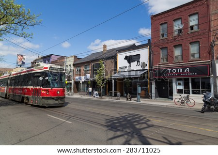 TORONTO, CANADA - 19TH MAY 2015: A view along Queen Street in Toronto showing businesses and buildings. People and a TTC Streetcar can be seen. - stock photo