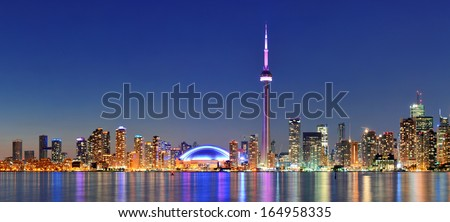 Toronto cityscape panorama at dusk over lake with colorful light.
