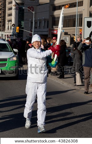 TORONTO - DECEMBER 17: Lindsay Leo  carrying Olympic torch at Yonge and Sheppard, on December 17, 2009 in North York (Toronto) - stock photo