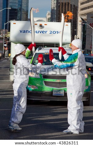 TORONTO - DECEMBER 17: Richard Peddie President and CEO of Maple Leafs Sports and Entertainment and Lindsay Leo passing Olympic flame at Yonge and Sheppard on December 17, 2009 in Toronto - stock photo