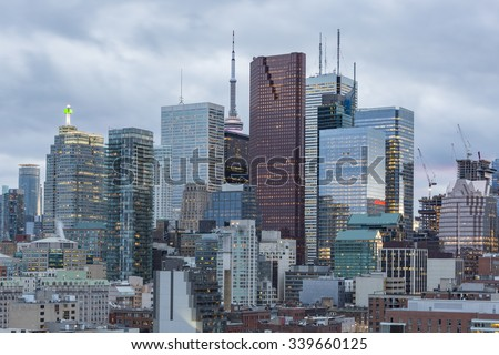 Toronto Financial District skyscrapers and  CN Tower apex on a cloudy background at sunset - stock photo