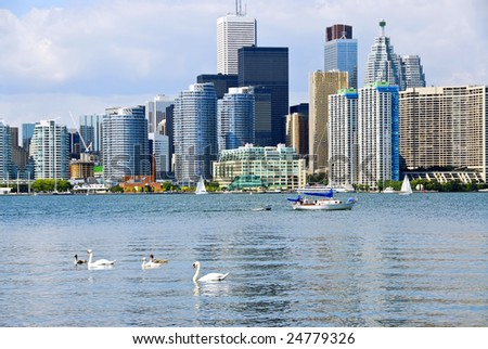 Toronto harbor skyline with skyscrapers sailboat and swans - stock photo