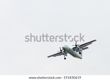 TORONTO INTERNATIONAL AIRPORT - MAY 9, 2014: Canada Express turboprop plane with engaged landing gear landing at Toronto Pearson International airport.
