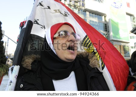 TORONTO - JANUARY 21: A old Egyptian woman chanting slogans in a rally at Yonge and Dundas square during the global day of support for the Egyptian revolution on January 21 2012 in Toronto, Canada. - stock photo