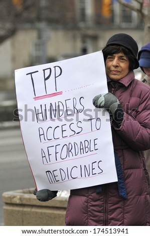 TORONTO-JANUARY 31: A protester holding sign to criticize TPP agreement  during a rally  to protest the proposed TPP  trade agreement and NAFTA  Agreement on January 31, 2014 in Toronto, Canada.
