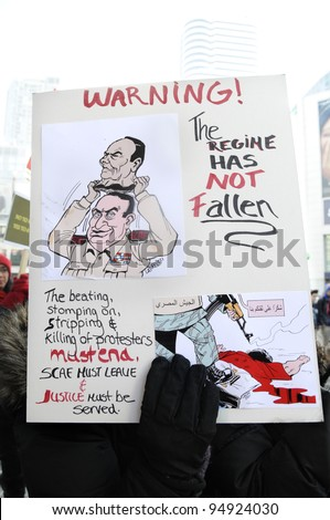 TORONTO - JANUARY 21: A protestor holding a cartooned placard denouncing killing of protesters during the global day of support for the Egyptian revolution on January 21 2012 in Toronto, Canada. - stock photo