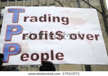 """TORONTO-JANUARY 31: A  sign saying """"trading profits over people""""  during a rally  to protest the proposed TPP  trade agreement and NAFTA  Agreement on January 31, 2014 in Toronto, Canada. - stock photo"""