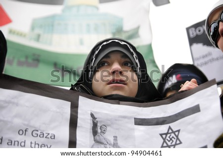 TORONTO - JANUARY 10:  A unidentified protestor holding a banner comparing the Holocaust during World War II with current occupation in Palestine  during a rally in Toronto on January 10 2009 in Toronto, Canada.