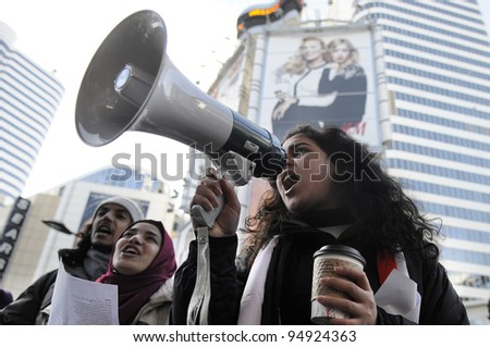 TORONTO - JANUARY 21: Egyptian teens  participating in a rally at Yonge and Dundas square   during the global day of support for the Egyptian revolution on January 21 2012 in Toronto, Canada. - stock photo
