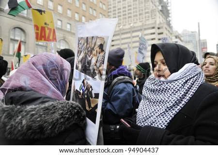 TORONTO - JANUARY 10: Two unidentified women having a conversion with pictures of Israeli atrocities during a rally to condemn the Israel occupation on Gaza on January 10 2009 in Toronto, Canada.