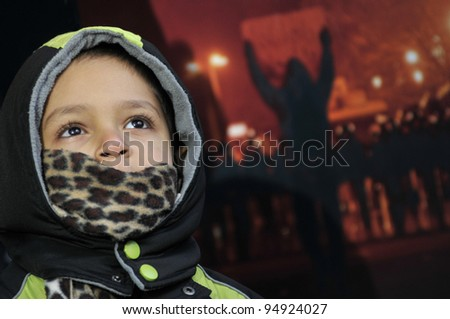 TORONTO - JANUARY 21: 4 year-old  unidentified Yemeni standing in front of a poster showing the Egyptian uprising during the global day of support for the Egyptian revolution on January 21 2012 in Toronto, Canada. - stock photo