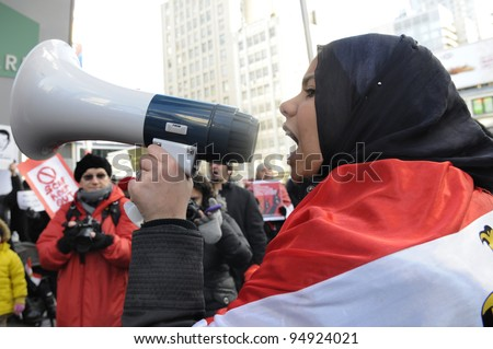 TORONTO - JANUARY 21:   Young Egyptians chanting slogans at Yonge and Dundas square during the global day of support for the Egyptian revolution on January 21 2012 in Toronto, Canada. - stock photo
