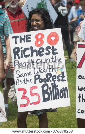"TORONTO - JULY 5 :  A girl with a sign stating the ""social wealth inequality"" during the Jobs,Justice and Climate rally on July  5, 2015 in Toronto, Canada."
