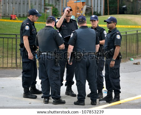 TORONTO-JULY 17: A group of police officers at the crime scene where shooting leaves 2 dead and 21 injured on July 17, 2012 in Toronto - stock photo