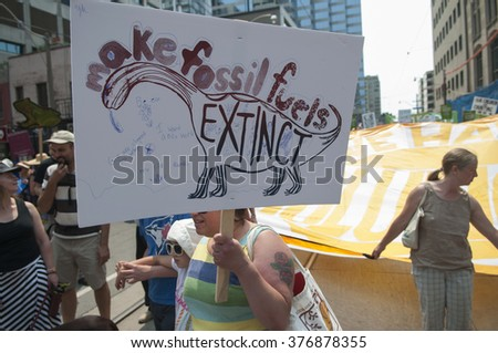 TORONTO - JULY 5 : A woman with a sign asking to stop the use of fossil fuel  during the Jobs,Justice and Climate rally on July  5, 2015 in Toronto, Canada.