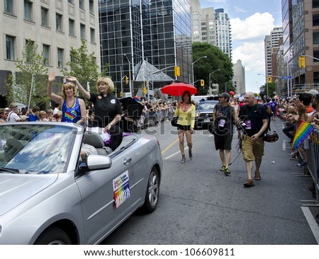 TORONTO-JULY 1: Cheri DiNovo and Laurel Broten during the 32 Pride Parade which celebrates the history, diversity and future of the  gay community as seen on July 1, 2012 in Toronto - stock photo