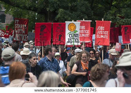 TORONTO - JULY 5 : People concerned with  Jobs, Justice and Climate walking with signs and banners  during the Jobs,Justice and Climate rally on July  5, 2015 in Toronto, Canada.