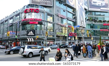 TORONTO- JULY 12: People in Dundas Square on October 20, 2013 in Toronto. Dundas Square is a commercial and public square that hosts many events and it is one of Toronto's main attraction. - stock photo