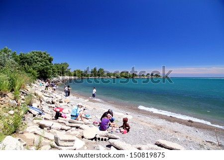 TORONTO - JULY 27: People on a beach on the Lake Ontario on July 27, 2013 in Toronto. Lake Ontario is the easternmost of the Great Lakes and the smallest in surface area (7,340 sq mi, 18,960 km2). - stock photo