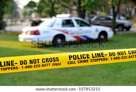 TORONTO-JULY 17: Police line Do not cross tape with police car in the background at the crime scene where  shooting leaves 2 dead and 21 injured on July 17, 2012 in Toronto - stock photo