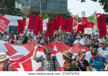 "TORONTO - JULY 5 :  Protesters under the banner of "" no one is illegal""-a movement to protect the illegal immigrants during the Jobs,Justice and Climate rally on July  5, 2015 in Toronto, Canada."