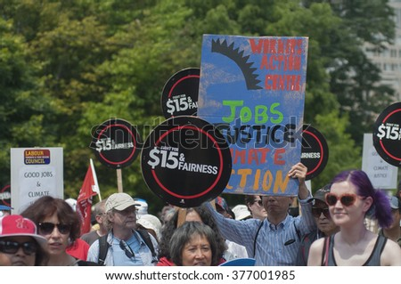 TORONTO - JULY 5 :  Supporters asking for the minimum wage in Canada to be raised to !%/hr during the Jobs,Justice and Climate rally on July  5, 2015 in Toronto, Canada.