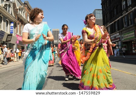 TORONTO - JULY 13:  Women disciples dancing on the streets  during the 41st Annual Festival of India on July 13, 2013 in Toronto-Canada. - stock photo