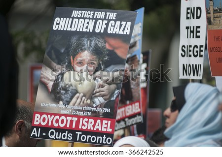 TORONTO-JULY 11: Women marching with signs asking for justice for the Palestinian children during the Al-Quds day rally on July 11, 2015 in Toronto,Canada. - stock photo