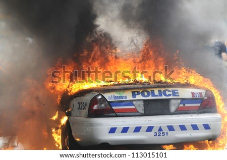 TORONTO-JUNE 26: A burning police car  during the G20 Protest on June 26, 2010 in Toronto, Canada. - stock photo