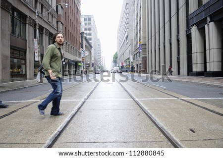 TORONTO-JUNE 26:   A man crosses an empty street which is otherwise clogged with traffic during the G20 event  on June 26, 2010 in Toronto, Canada. - stock photo