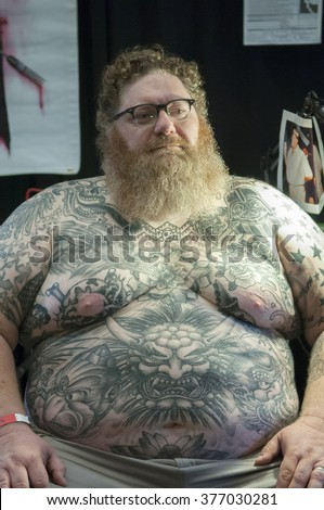 TORONTO - JUNE 19 :  A man  with tattoos all around his upper body part waiting for the artist during the Toronto Tattoo convention on June 19, 2015 in Toronto, Canada.