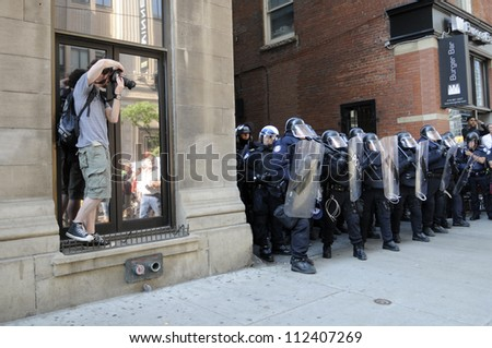 TORONTO-JUNE 25: A  photojournalist taking pictures of the riot police during the G20 Protest on June 25, 2010 in Toronto, Canada. - stock photo