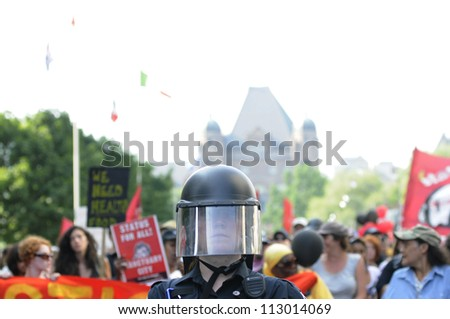 TORONTO-JUNE 25:  A Police officer wearing protective helmet guiding a huge rally through the streets of Toronto during the G20 Protest on June 25, 2010 in Toronto, Canada. - stock photo