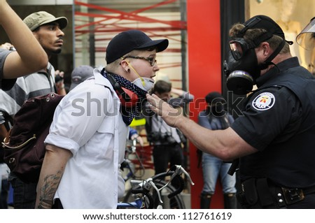 TORONTO-JUNE 26:   A protester having an argument with a police officer during the G20 Protest on June 26 2010 in Toronto, Canada. - stock photo